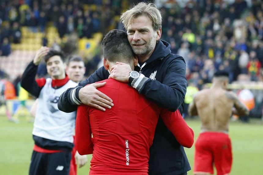 Juergen Klopp - minus his glasses - celebrates with players after Liverpool's win.