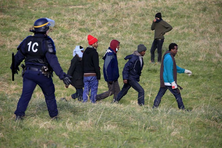 Police stop Calais migrants as they try to board lorries bound for Britain on Jan 21, 2016.