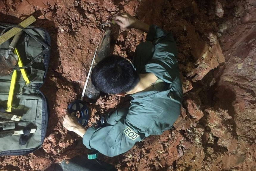 A member of SAF's Explosive Ordnance Disposal team measuring the suspected war relic.