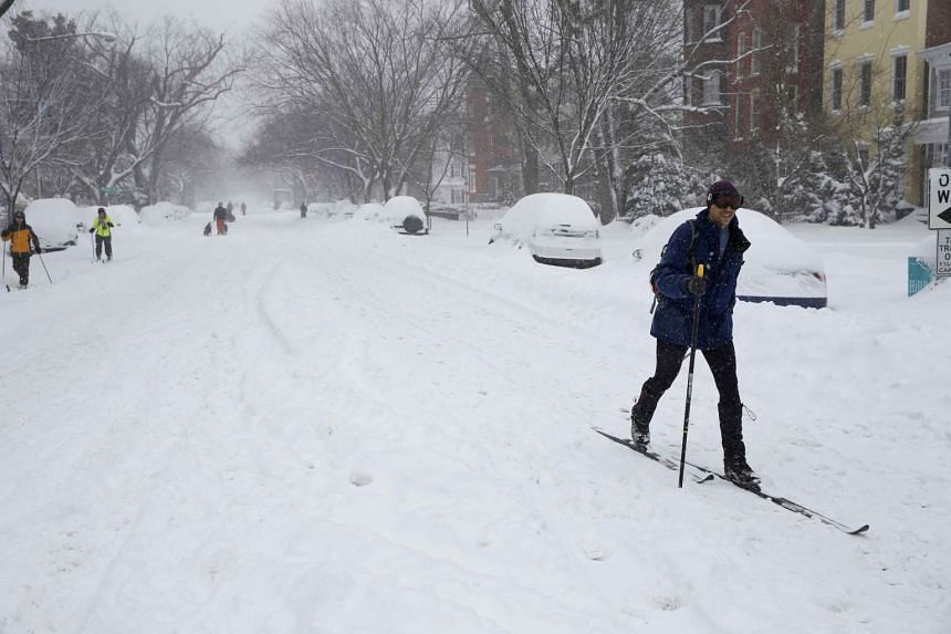 A person skis down a street as snow continues to fall in Washington.