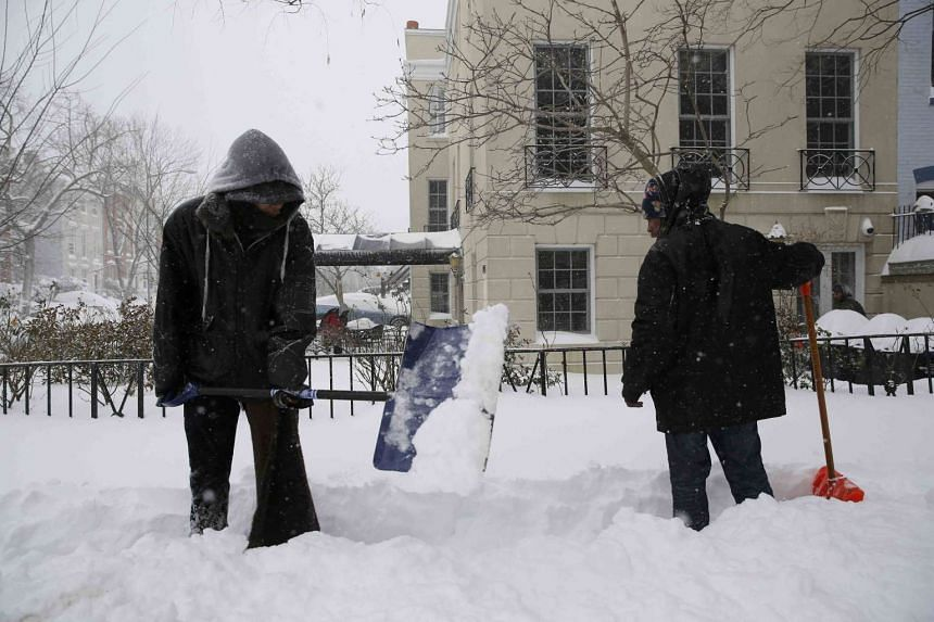 Residents shovel snow on a pavement in Washington.