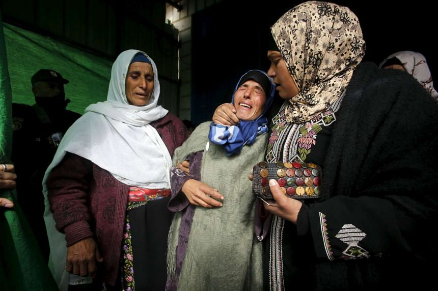 The mother (centre) of the 13-year-old Palestinian girl mourns during her funeral in the West Bank town of Yatta on Jan 24, 2016.