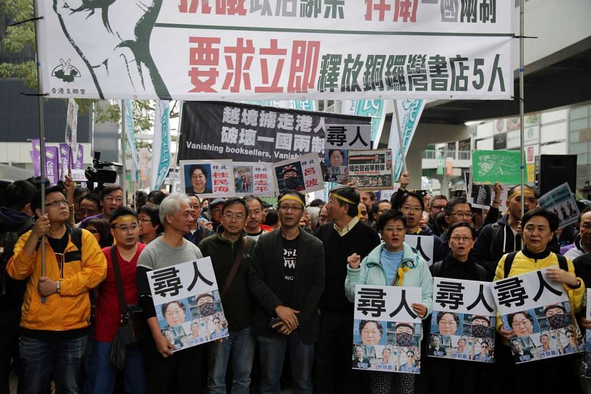 People hold placards with some of the missing booksellers from Hong Kong during a protest on Jan 10, 2016.