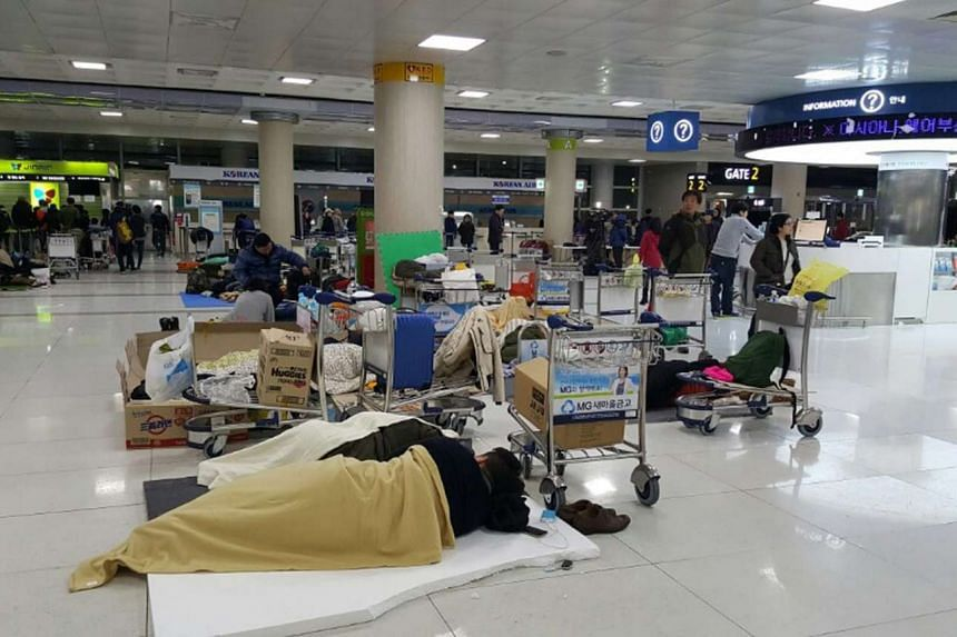 When flights were grounded, passengers slept in a departure hall at Jeju International Airport in South Korea on Jan 25, 2016.