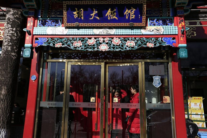 Chinese hostesses are seen behind the door of a branch of Huda Restaurant chain in Beijing, China, on Jan 23, 2016.
