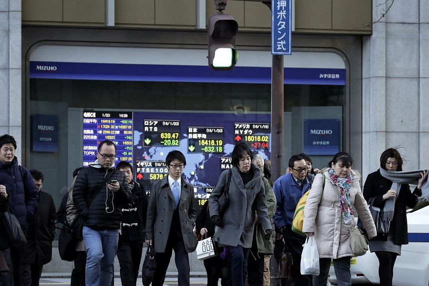 Pedestrians cross a road in front of an electronic stock board outside a securities firm in Tokyo.