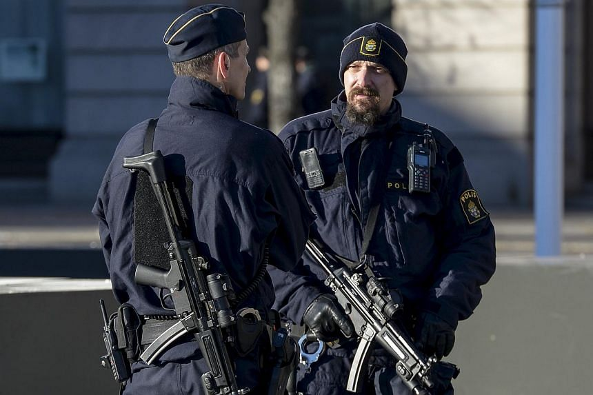 Armed police provide security at a memorial event to honour victims of the Paris attacks, in central Stockholm, Sweden, on Nov 21, 2015.
