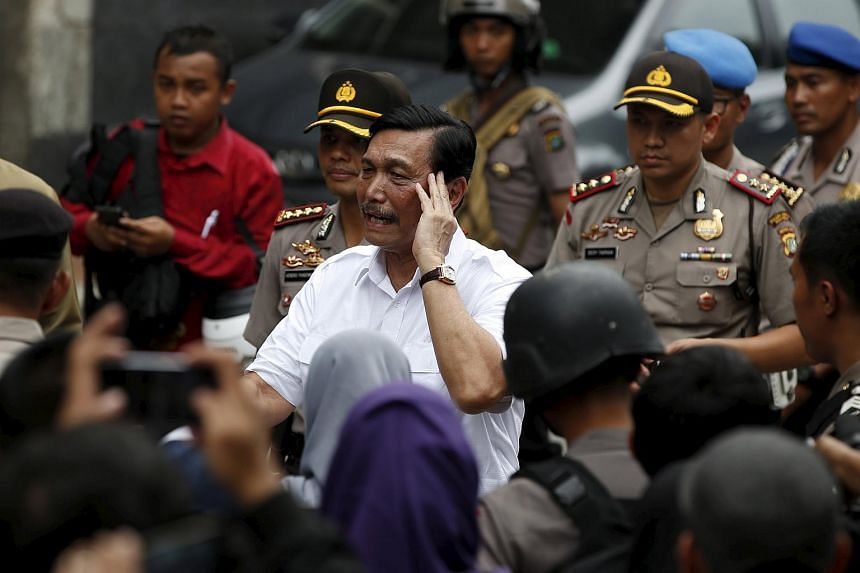 Indonesia's chief security minister Luhut Pandjaitan (centre) visits the site of an attack in central Jakarta.