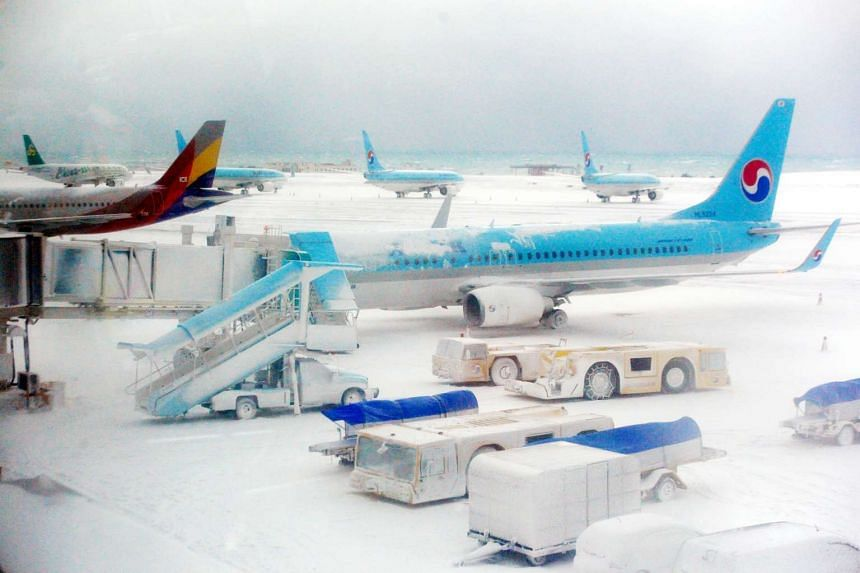 Planes on the snow covered landing strip at Jeju International Airport on Jan 24, 2016.
