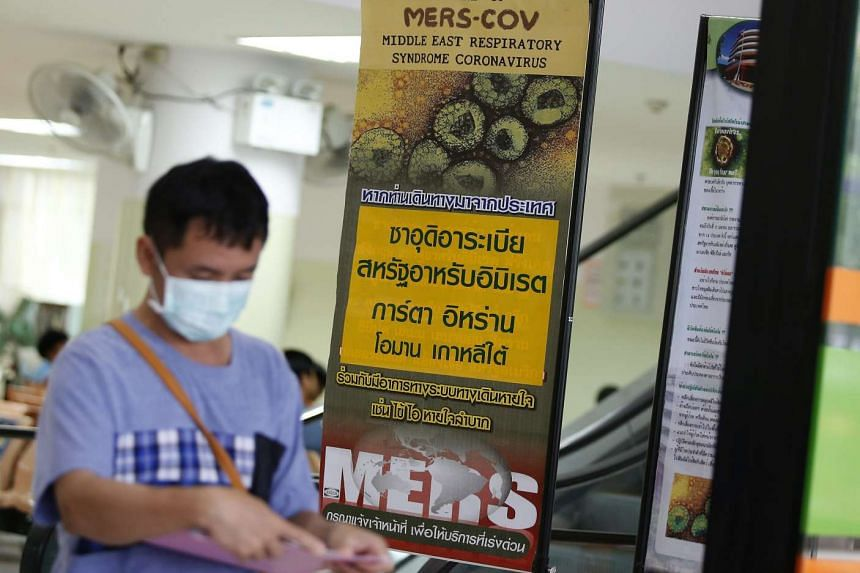 A Thai man wears a protective mask as he walks next to signs giving information on Mers in Bangkok.