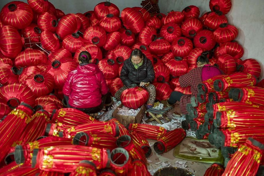 Workers make red lanterns at a factory in the village of Tuntou.