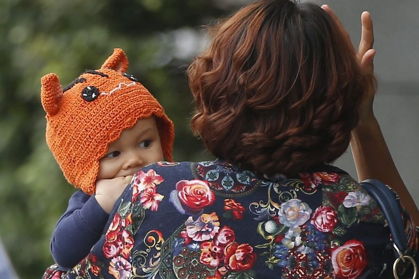 A woman carries a toddler wearing a knitted hat along a street in Bangkok, during unusally cold weather, on Jan 25, 2016.