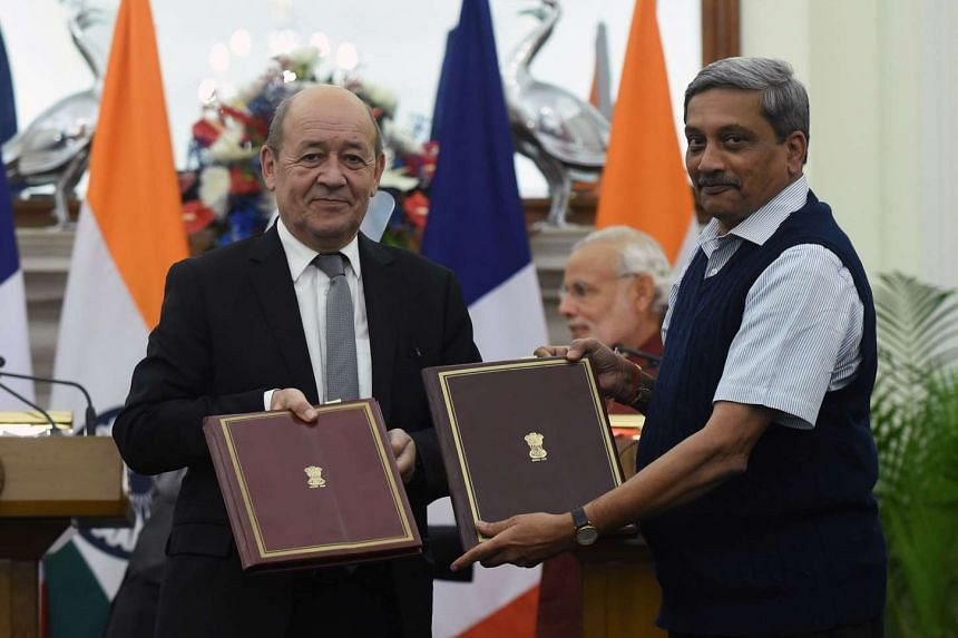 French Defence Minister Jean-Yves Le Drian (left) and Indian counterpart Manohar Parrikar showing the agreements for the purchase of Rafale jet fighters in New Delhi on Jan 25, 2016.