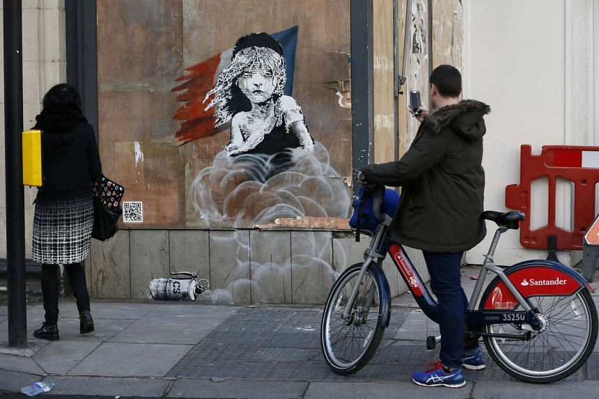 People photograph a new graffiti mural attributed to Banksy, opposite the French embassy in London.
