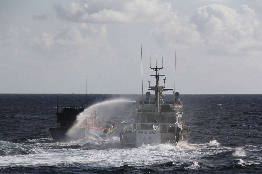 A handout photo showing Taiwan's coastguard (right) spraying a Vietnamese fishing boat with a water cannon.