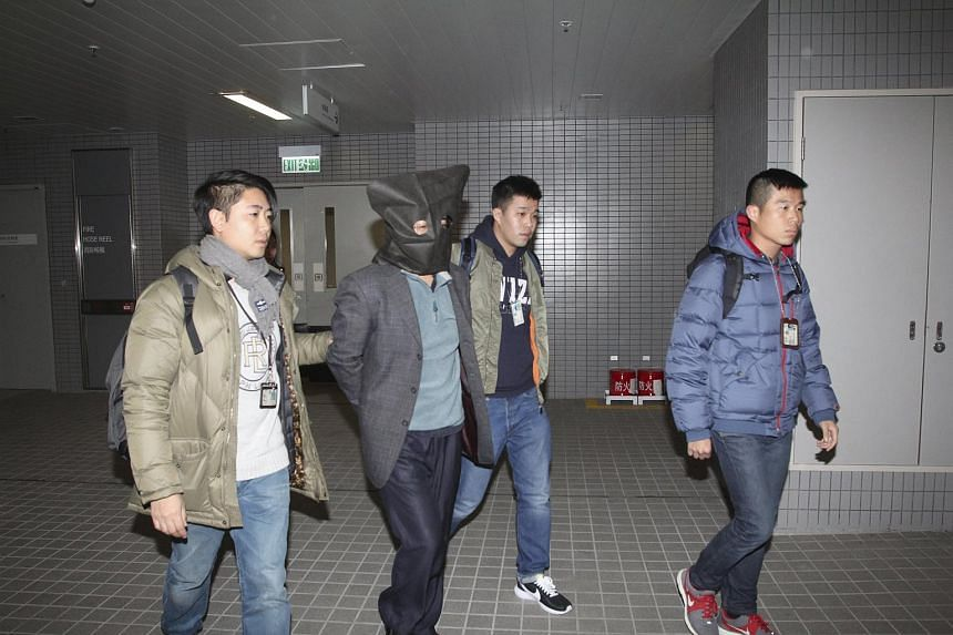 Shi Deyun (second from left) is escorted by police officers in Hong Kong on Jan 24, 2016.