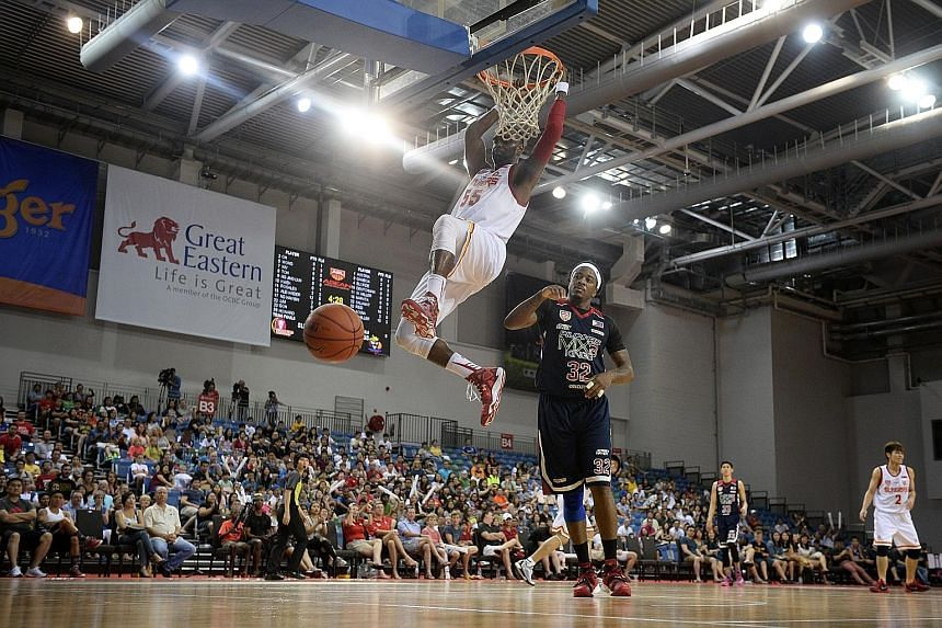 The Singapore Slingers centre Justin Howard (white jersey) dunks home two of his game-high 24 points in his team's convincing 80-58 Asean Basketball League win over the Pilipinas MX3 Kings at the OCBC Arena yesterday afternoon. The table-topping Slin