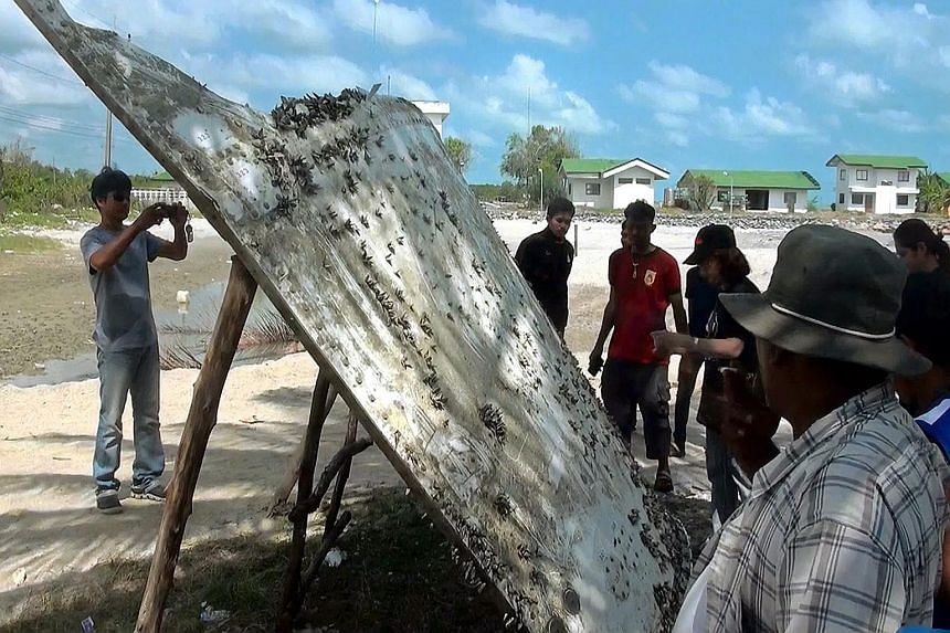 Villagers inspecting the piece of suspected airplane wreckage at a beach in Nakhon Si Thammarat province, Thailand, on Saturday. Experts said while powerful currents sweeping the Indian Ocean could deposit debris thousands of kilometres away, wreckag