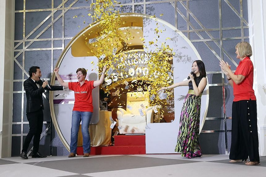 """British administrator Linda Tobin, 52, with hosts Chua Enlai (far left) and Lin Peifen, emerging as the winner of a million dollars at Changi Airport. Briton Tracy Tomlinson (left), 52, was the other remaining finalist in the """"Be a Changi Millionaire"""