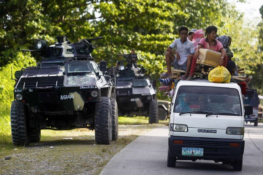 People driving past an armoured personnel carrier (APC) in Kauran, Ampatuan in the southern Philippine province of Maguindanao, on Dec 24, 2015.