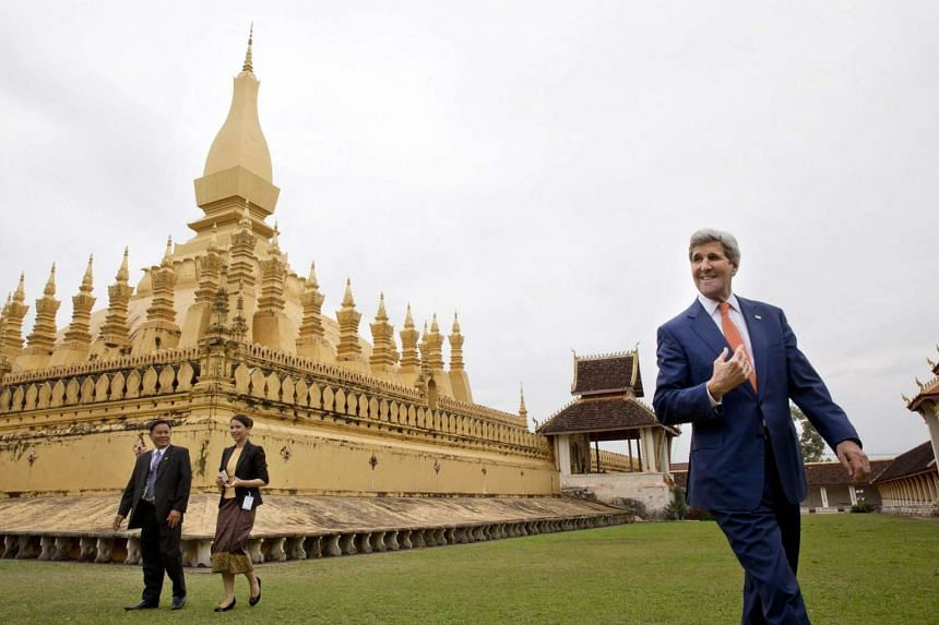 """US Secretary of State John Kerry (R) tours the That Luang Stupa or """"Pha Tha Luang,"""" with Phouvieng Phothisane, acting director of the Vientiane Museums (far L) and Tata Keovilay (2nd L), attached to the US embassy, in Vientiane on January 25, 2016. T"""