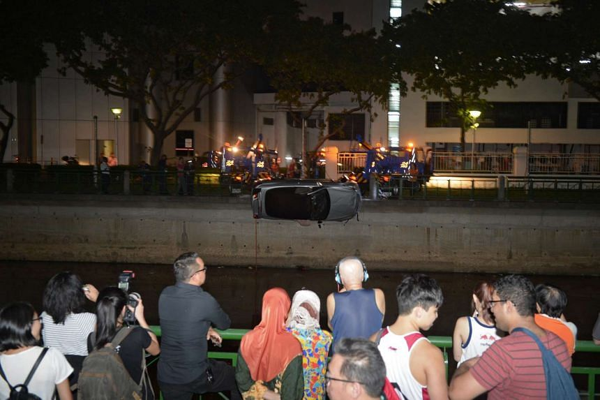 People watch as a car which crashed into Alexandra Canal is hoisted by three tow trucks.