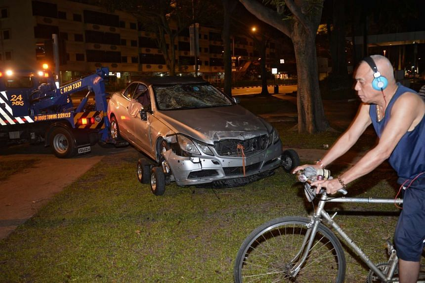 A man cycles past the car which crashed into Alexandra Canal on Jan 25, 2016.