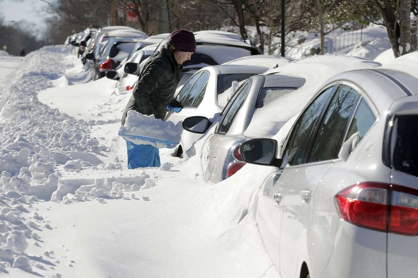 A woman digs he snow out from around her car in Washington DC on Sunday, after 45.2 cm fell on the US capital, tying as the fourth-largest snowfall in the city's history.