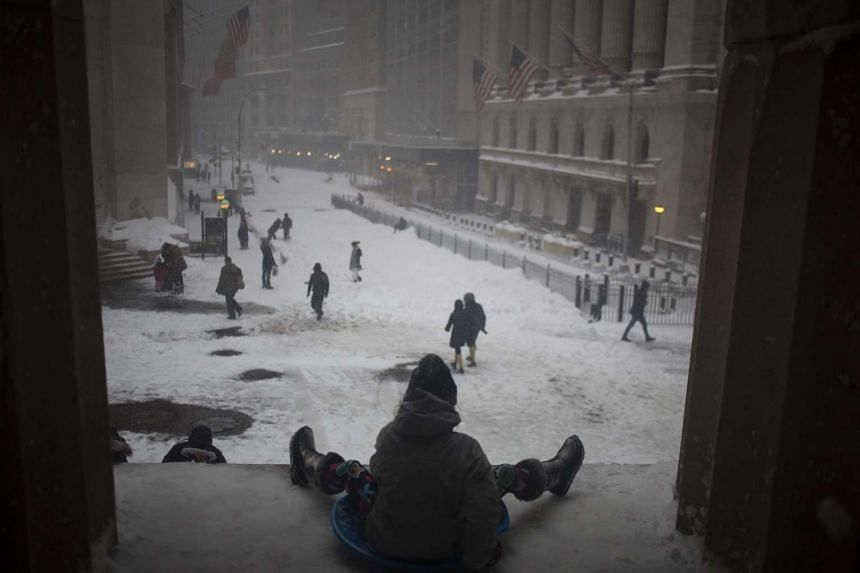 Kids slide down a hill in the snow near the New York Stock Exchange (NYSE) in Lower Manhattan, New York over the weekend.
