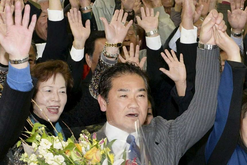Ginowan mayor Atsushi Sakima raises his hands after he was re-elected in Ginowan on the Japanese southern island of Okinawa on Sunday in a photo taken by Kyodo.