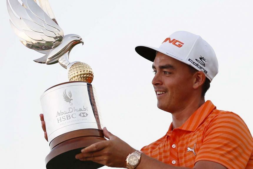 Rickie Fowler of the United States holds his trophy after winning the Abu Dhabi Golf championship on Sunday.