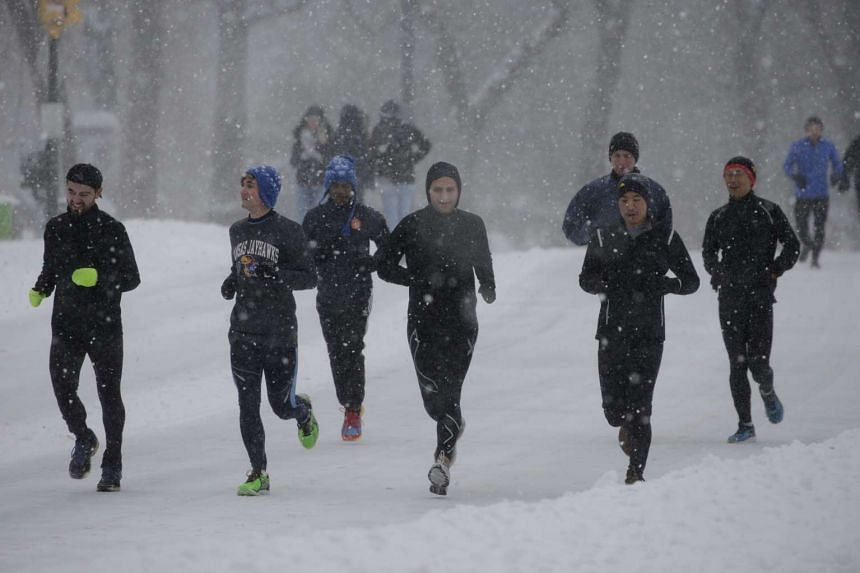 Runners run through Central Park during the major winter storm that slammed New York City on Saturday.