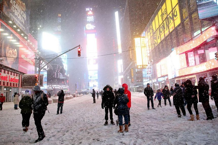 Pedestrians walk through the snowy streets near Times Square in New York City on Saturday.