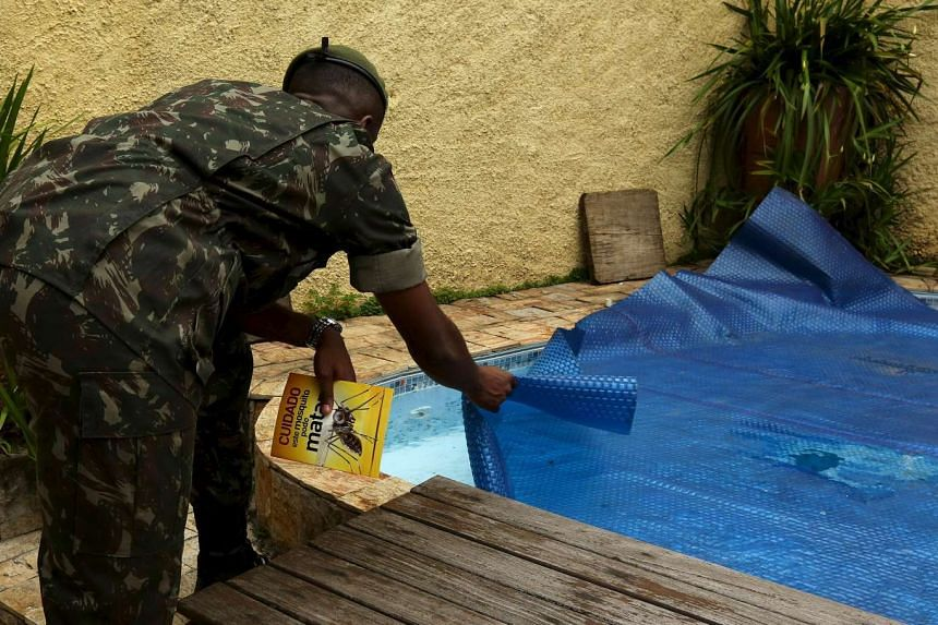 A Brazilian soldier searches for signs of mosquito larvae in a pool in Sao Paulo, Brazil on Jan 18.