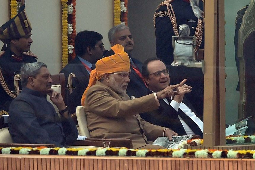 Indian Prime Minister Narendra Modi (centre) speaking with French President Francois Hollande while watching India's Republic Day parade on Jan 26, 2016.