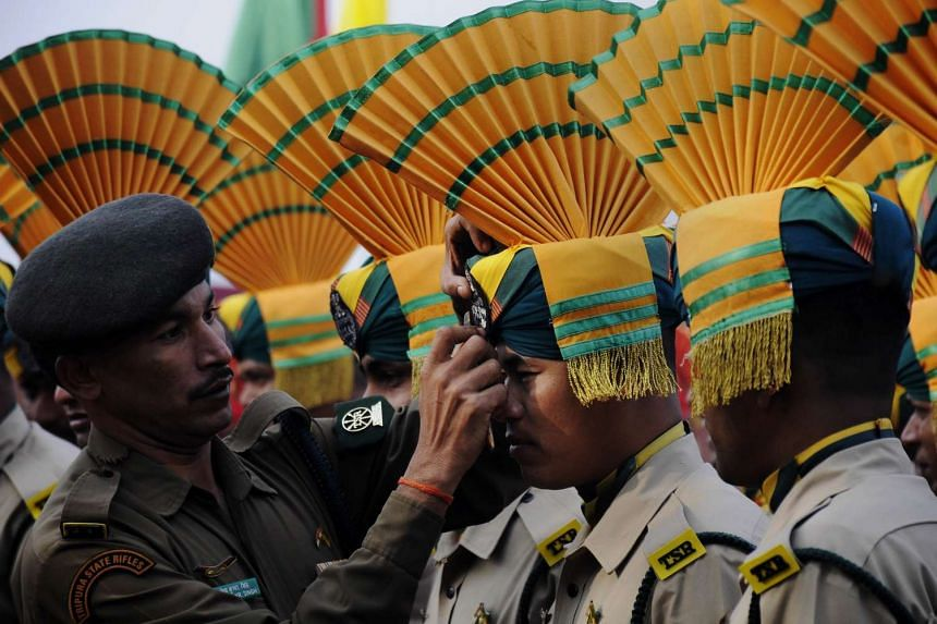 An Indian paramilitary personnel adjusts the headdress of a colleague during a Republic Day parade on Jan 26, 2016.