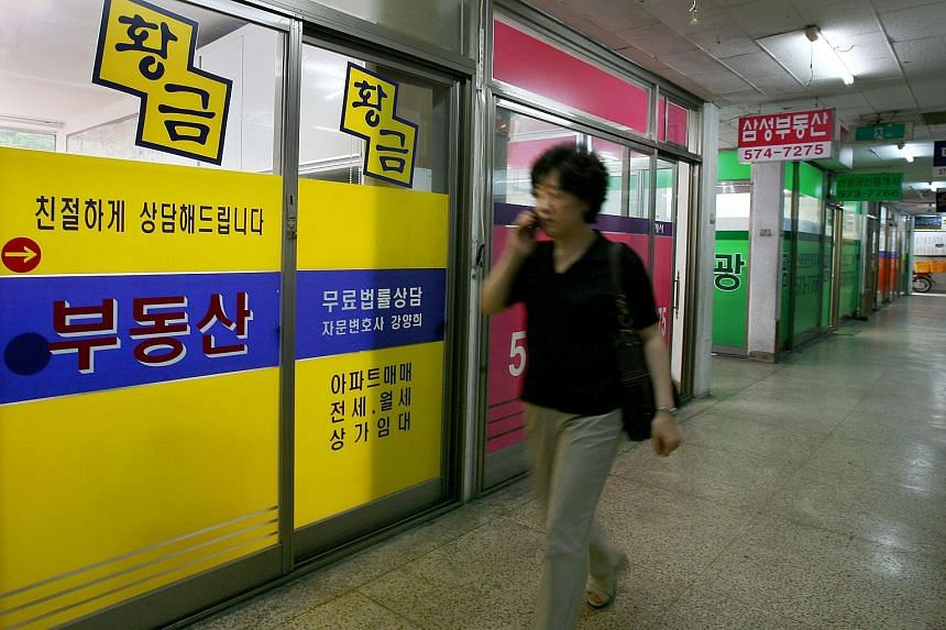 A woman walks past real estate agents' offices in the Gaepo-dong residential complex in Seoul.