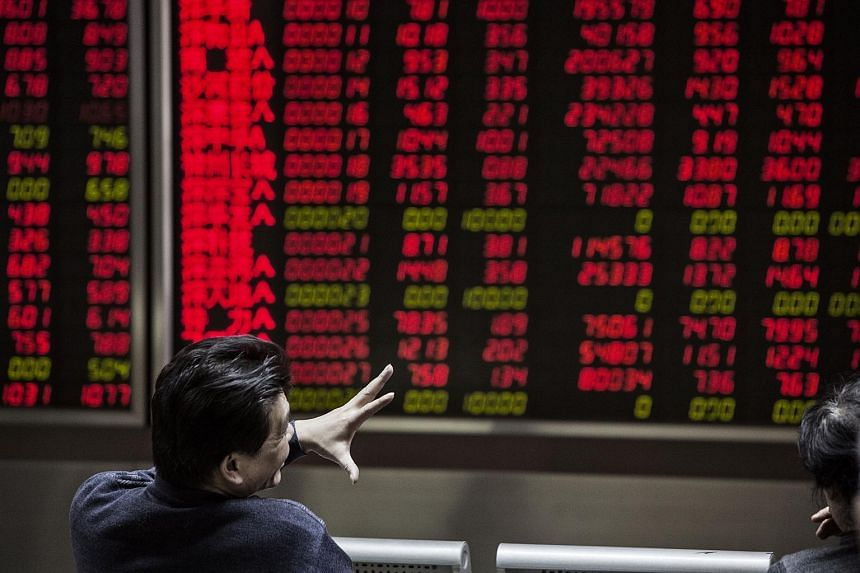 A man gestures in front of electronic boards displaying stock information at a securities brokerage in Beijing.