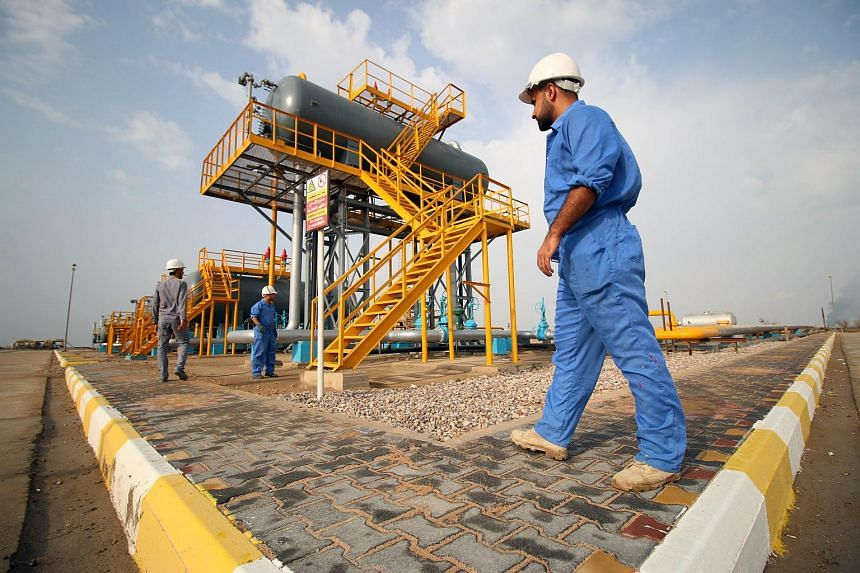 Iraqi labourers work at an oil refinery in the southern town Nasiriyah on Oct 30, 2015.