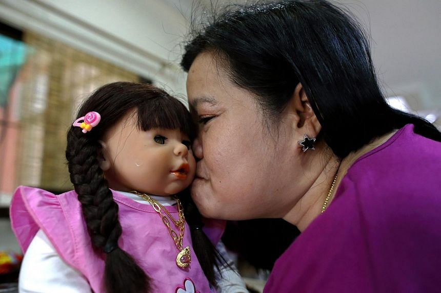 Thai devotee Ratchada Mahanavanont kissing her Child Angels Doll at her house in Bangkok, Thailand, on Jan 24, 2016.