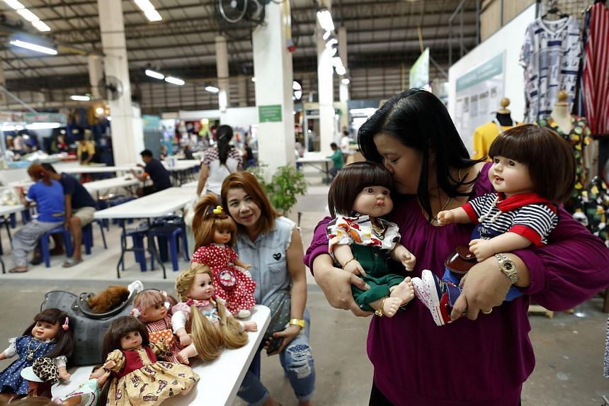 Thai devotees Ratchada Mahanavanont (right) kissing her Child Angels Dolls next to her friend, Nita Kangvanchaivanich, at a market in Bangkok, Thailand, on Jan 24, 2016.