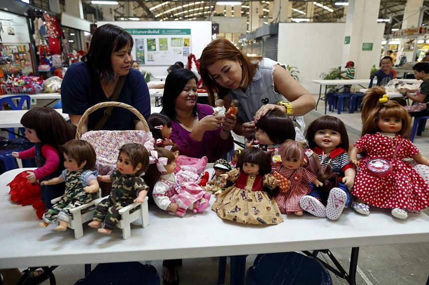 Three Thai devotees, Ratchada Mahanavanont (centre) talking to her friends Nipaporn Pornchaipimolpunt (left) and Nita Kangvanchaivanich (right), with their Child Angels dolls at a market in Bangkok, Thailand, on Jan 24, 2016.