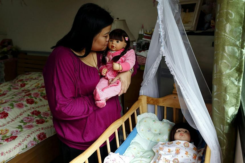 Thai devotee Ratchada Mahanavanont cradling her Child Angels Dolls at her house in Bangkok, Thailand, on Jan 24, 2016.