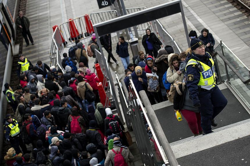 Police organise the line of refugees from the trains arriving from Denmark at the Hyllie train station outside Malmo, Sweden, on Nov 19, 2015.