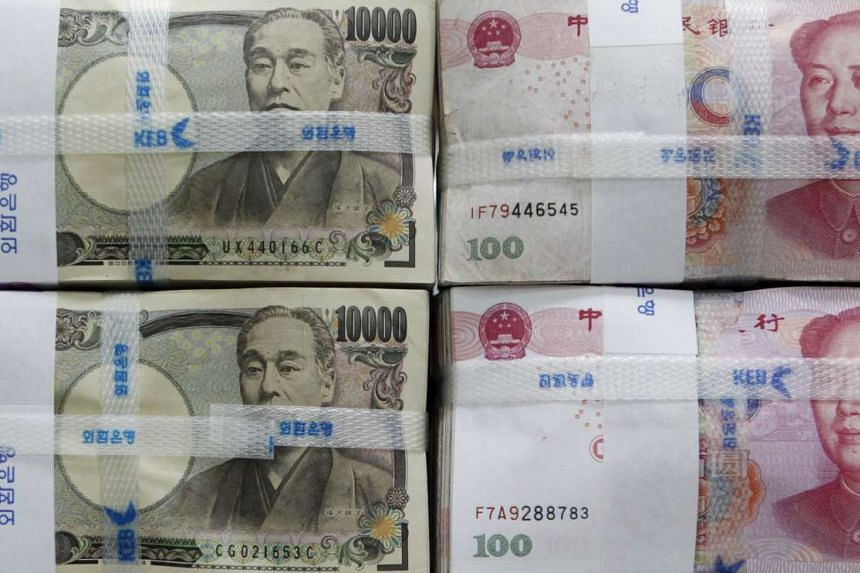 Japanese yen notes (left) and Chinese yuan notes.