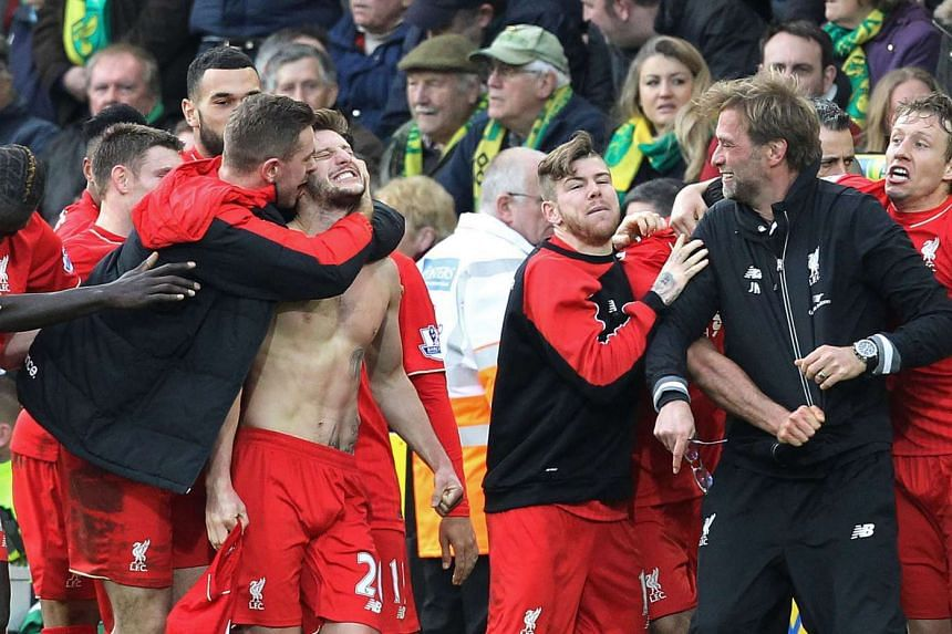 Liverpool's Adam Lallana (centre) celebrates scoring his late winning goal with teammates and manager Jurgen Klopp during the English Premier League football against Norwich City.