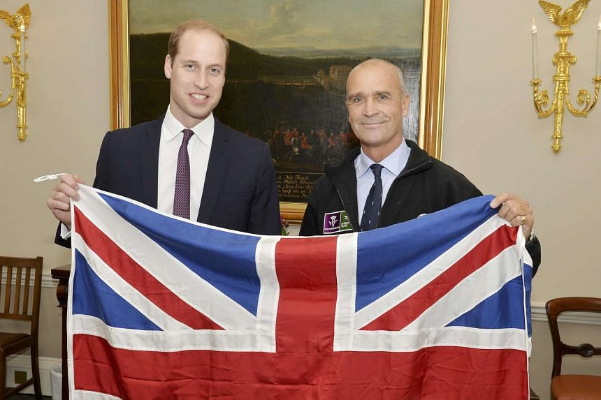 Britain's Prince William (left) holds a Union flag with explorer Henry Worsley at Kensington Palace in London, on Oct 19, 2015.