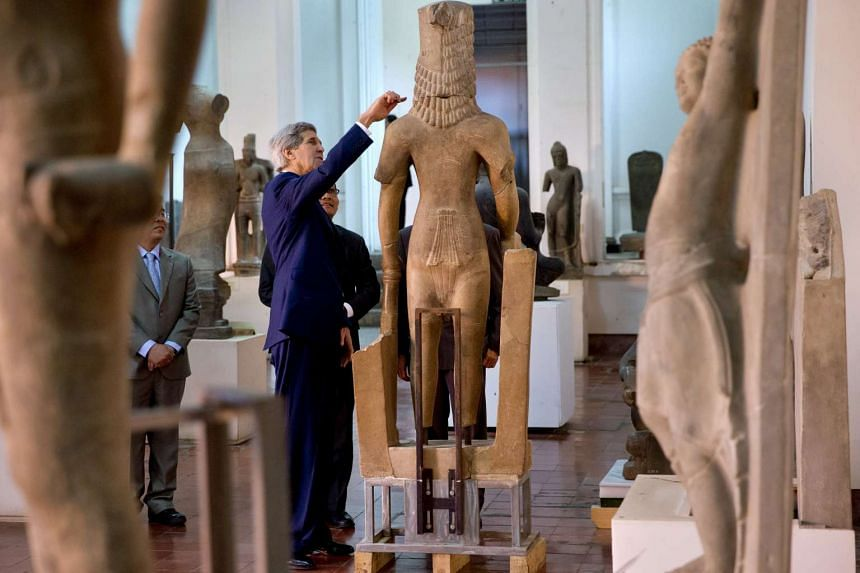 US Secretary of State John Kerry looks at a statue while touring the National Museum of Cambodia in Phnom Penh.