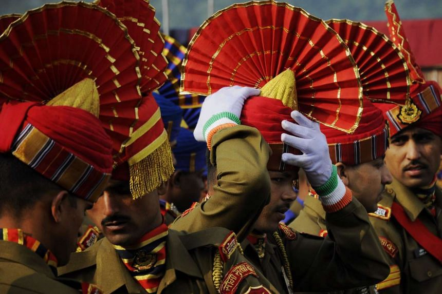 An Indian paramilitary Border Security Force personnel adjusts his headdress for the country's 67th Republic Day parade.