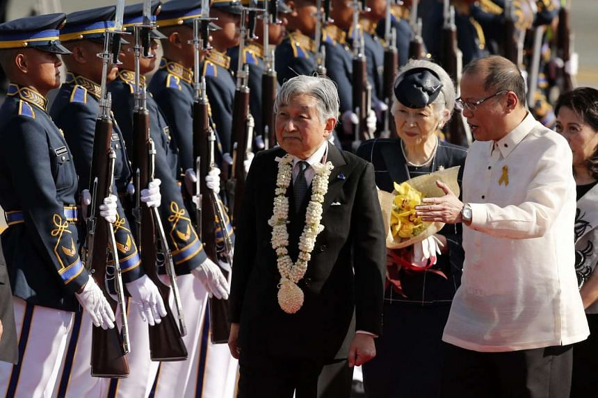 Japan's Emperor Akihito (centre) and Empress Michiko (second from right) are greeted by President Benigno Aquino III (right) at Manila's international airport.